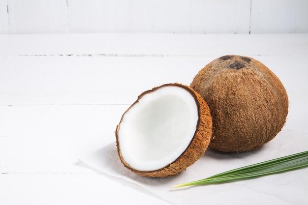 코코넛 절반과 흰색 나무 테이블에 나뭇잎