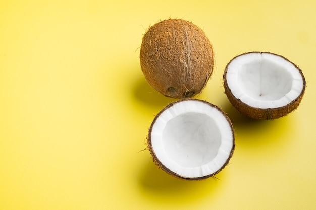 노란색 질감 된 여름 배경에 절반 세트 코코넛, 상위 뷰 평면 누워, 텍스트 복사 공간