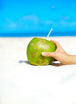 Coconut with hand on white beach