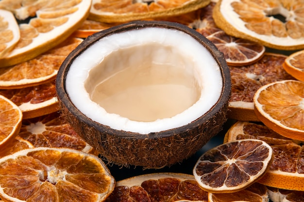 Coconut with natural milk on a background of dried citrus fruits