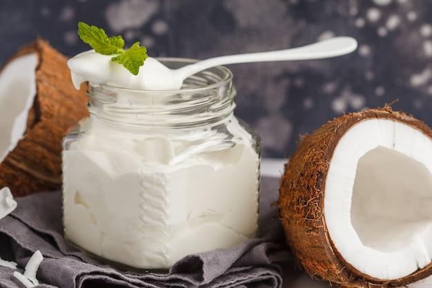 Coconut yogurt in a glass jar on a dark background, copy space, macro. healthy vegan food concept.
