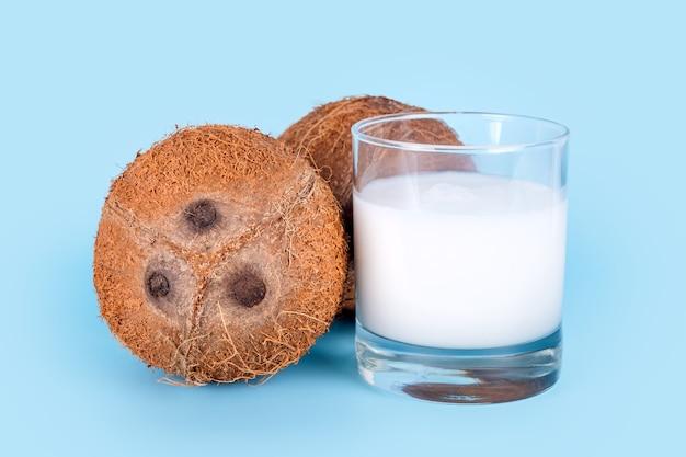 ココナッツと青い背景の上のココナッツミルクのガラス。健康的なビーガンフード、乳糖を含まない食事、代用乳。
