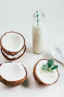 흰색 배경에 병에 코코넛과 코코넛 밀크