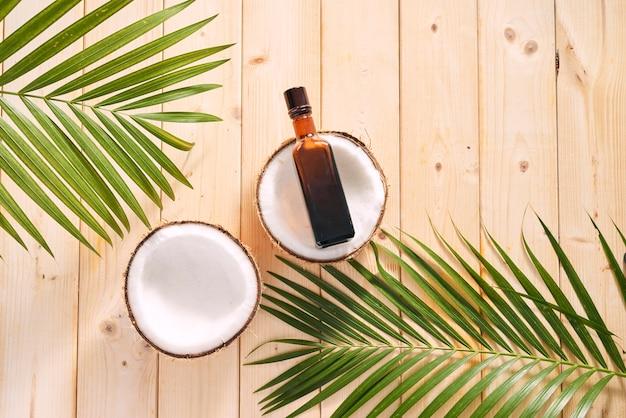 코코넛과 코코넛 오일은 나무 배경에 있습니다.