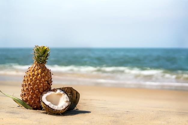 바다 모래에 코코넛과 파인애플. 아름다운 열대 풍경과 이국적인 과일이 있는 정물.