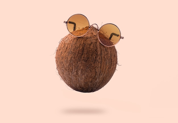 Coconuts are wearing sunglasses over pink background. concept vacation in the sunny tropics, levitating coconut with glasses