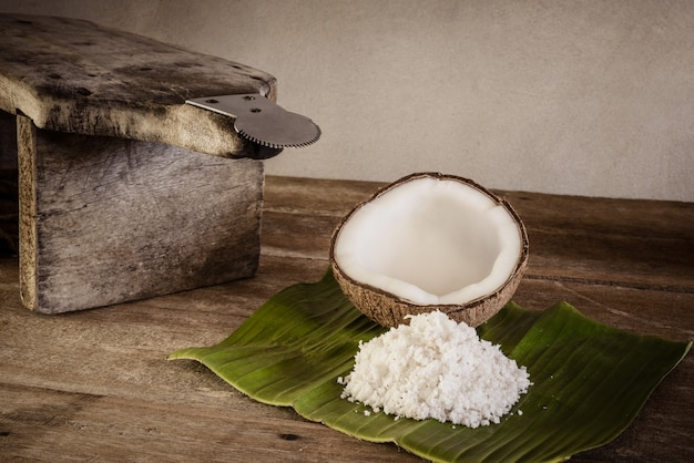 Coconuts and coconut flakes on banana leaf and coconut grater