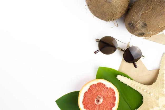 ココナッツ、グレープフルーツ、ヒトデ、緑の熱帯の葉、手紙、白のサングラス。夏のコンセプト