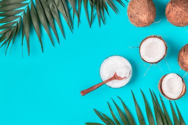 熱帯の葉とパステルカラーの背景にココナッツ