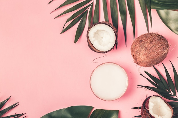 Coconuts on a pastel background with tropical leaves
