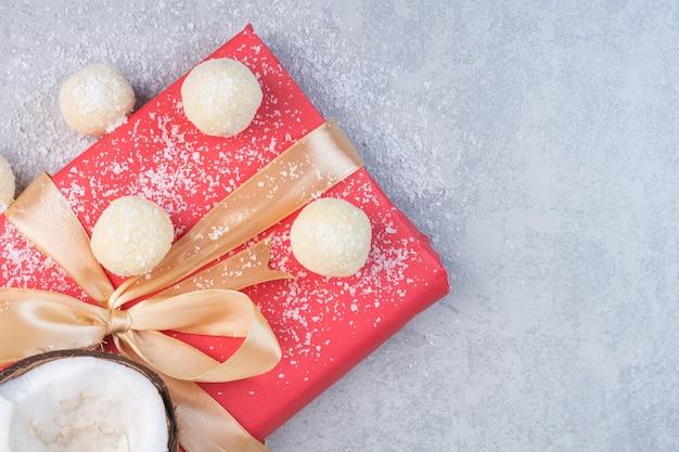 코코넛, 치즈, 아몬드 및 대리석 배경에 빨간색 선물 상자.