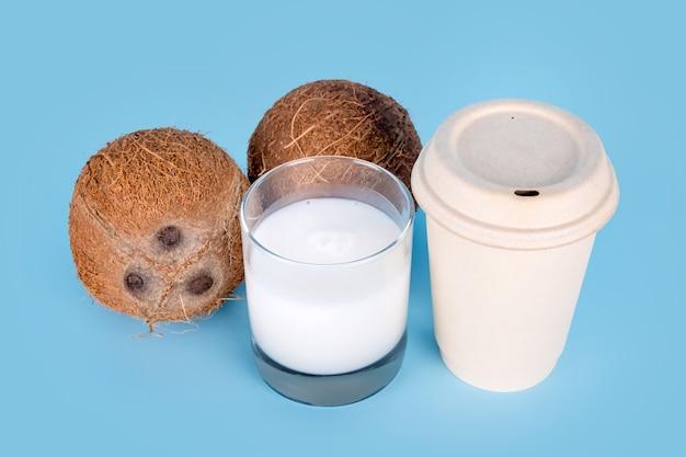 青い背景にココナッツミルクと紙のコーヒーカップのガラスとココナッツ。健康的なビーガンフード、乳糖を含まない食事、代替ミルク、持ち帰り用のコーヒー、ビーガンラテまたはココナッツカプチーノ。