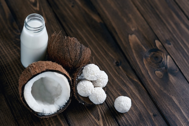 Coconuts with candies in coconut flakes and bottle of milk on wooden table.