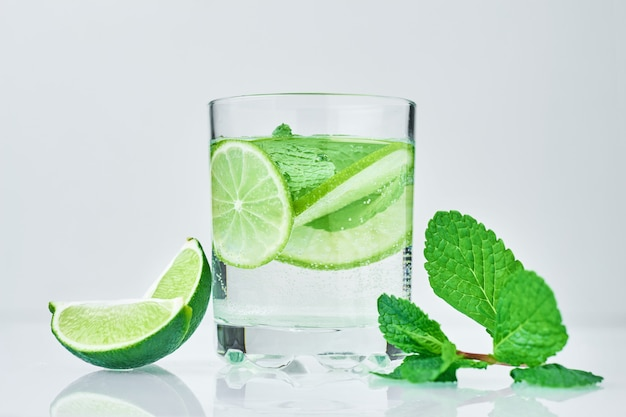 Coctail with lime and fresh mint on white