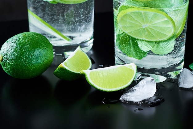 Coctail with lime and mint on dark background