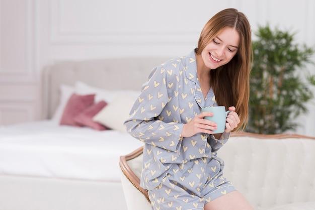 お茶のカップとcocuhに座っている若い女性