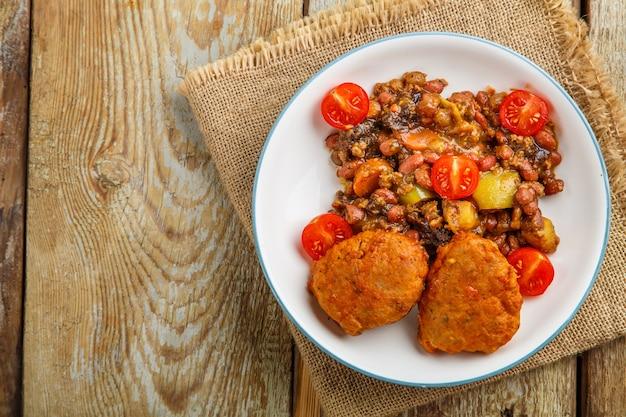 Котлеты из трески с картофелем и овощами на тарелке на салфетке.
