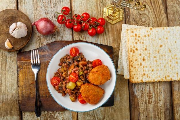 Котлеты из трески с тушеным картофелем и овощами на тарелке рядом с мацой и ингредиентами. горизонтальное фото