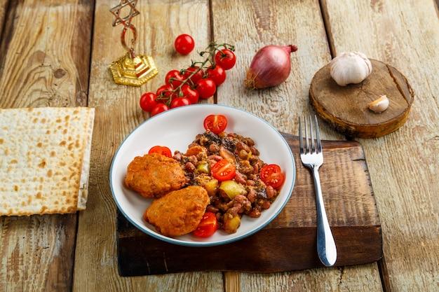 Котлеты из трески с тушеным картофелем и овощами на тарелке рядом с мацой и ингредиентами.