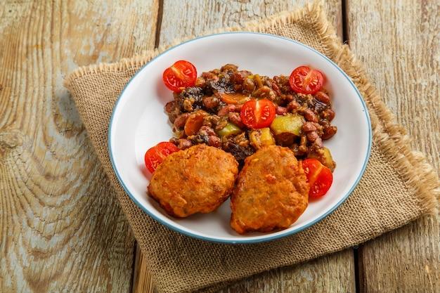 Котлеты из трески с тушеным картофелем и овощами на тарелке на салфетке.