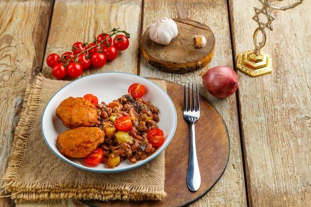 Котлеты из трески с тушеным картофелем и овощами на тарелке с ингредиентами.