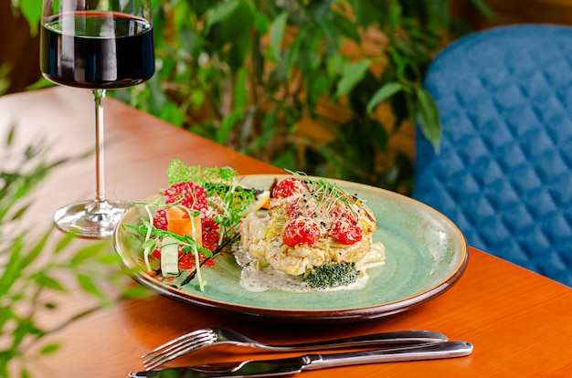 Cod fillet with tomatoes cherry and cheese, served with vegetables and red wine. mediterranean food concept