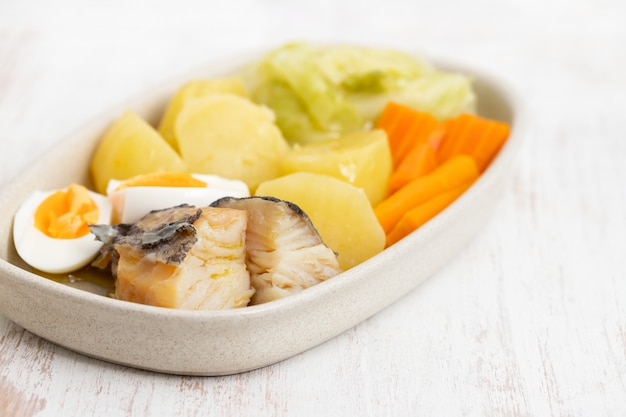Cod fish with boiled egg and vegetables on dish