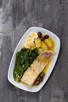 Рыба треска с капустой, картофелем и оливками на блюде