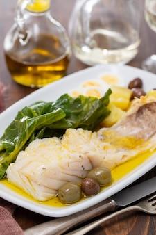 Треска с капустой, картофелем и оливками на блюде