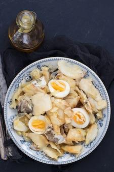 玉ねぎ、卵、オリーブオイルを皿に乗せたタラの魚