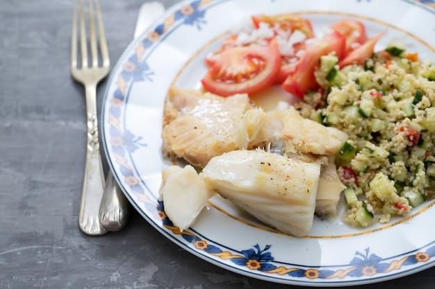 Треска с киноа и свежим салатом на блюде
