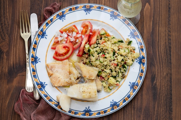 Cod fish with quinoa and fresh salad on dish