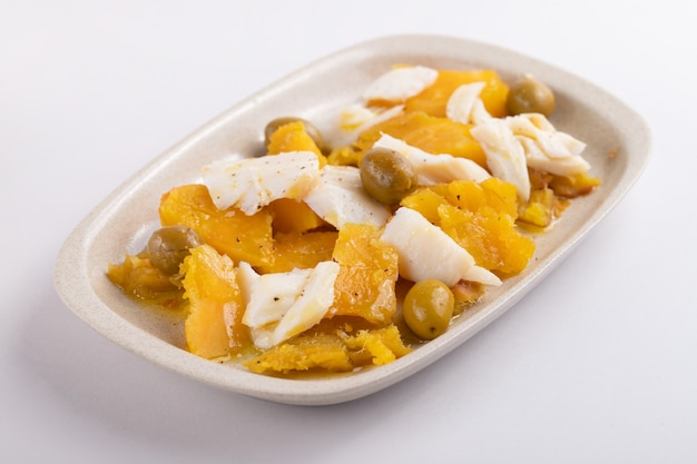 Cod fish with sweet potato and olives on dish on gray paper background