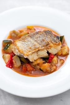 흰 접시에 야채와 대구 생선