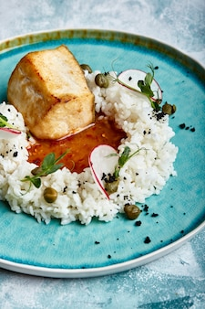 Cod steak with rice and sauce on a blue plate on a space of concrete.