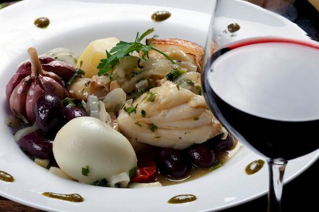 野菜と赤ワインのグラスとタラ