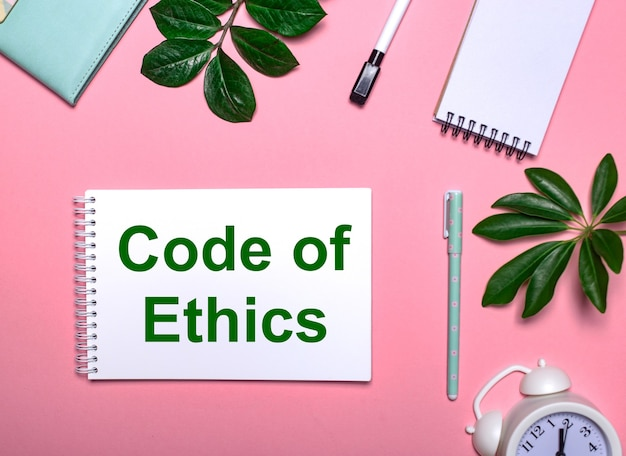 Code of ethics is written in green on a white notepad on a pink table surrounded by notepads, pens, white alarm clock and green leaves. educational concept