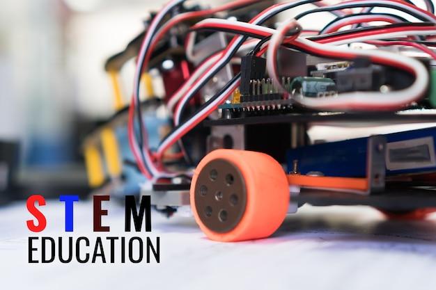 学校の実験室で機器を備えた電子ボード上で建設車のロボット工学を学習するコード。子供のための数学工学科学技術研究に関連するstem教育の概念