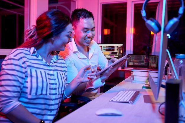 Кодеры делают небольшой перерыв и обсуждают смешные мемы и видео на цифровом планшете, розовый неоновый свет