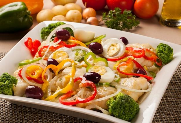Треска - рыбное филе в соусе и овощах на столе.