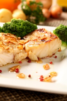 Codfish - fish fillet in sauce with garlic and vegetables