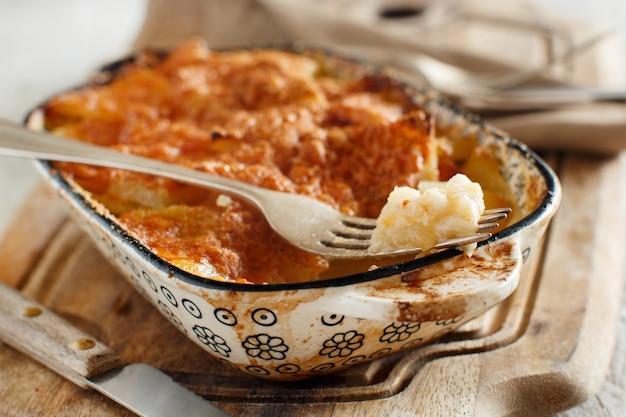 小さなキャセロールのオーブンで調理されたジャガイモとタラまたはバッカラ
