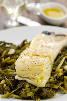 Codfish with olives and greens on white plate on wooden background