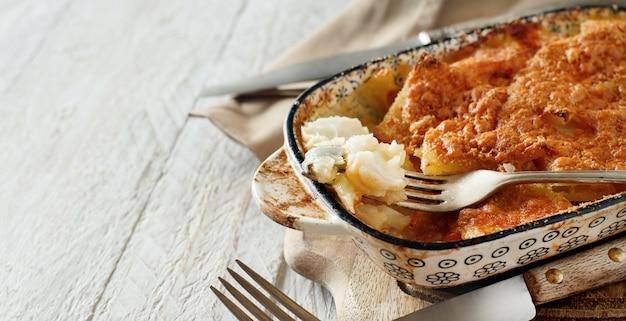 オーブンで調理されたジャガイモとタラのクローズアップ