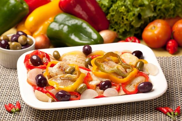 Треска с овощами и ингредиентами на поверхности