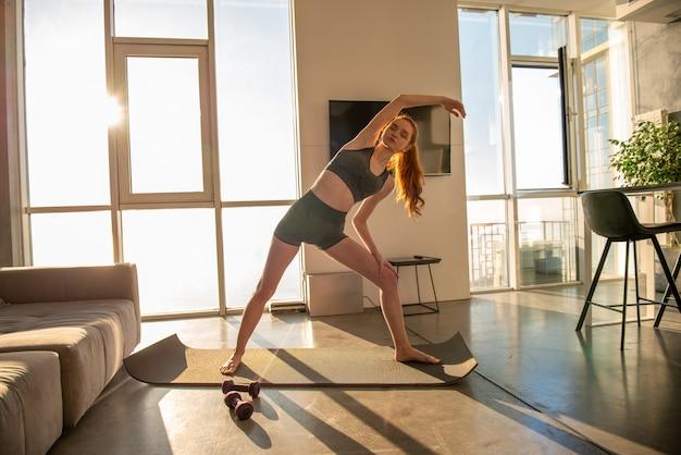 Молодая девушка делает гимнастику упражнения во время восхода солнца. она находится дома из-за карантин коронавируса codiv-19