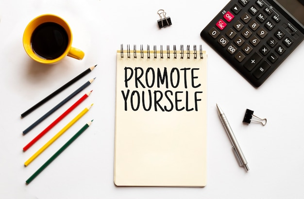 白い背景の上のコーヒーカップcalculatornotepadpenと鉛筆ビジネスコンセプトテキストあなた自身を宣伝する
