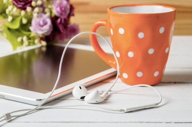 白い木製のテーブルにcofeeのオレンジ色のカップを持つ耳ポッドヘッドホンタブレット