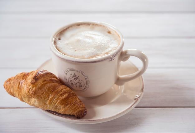 커피와 크루아상 나무 배경 아침 식사