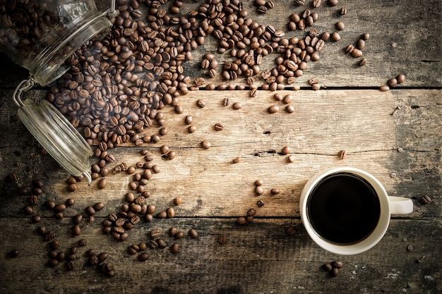 Кофейные бобы на гранж-дереве с фоном чашки